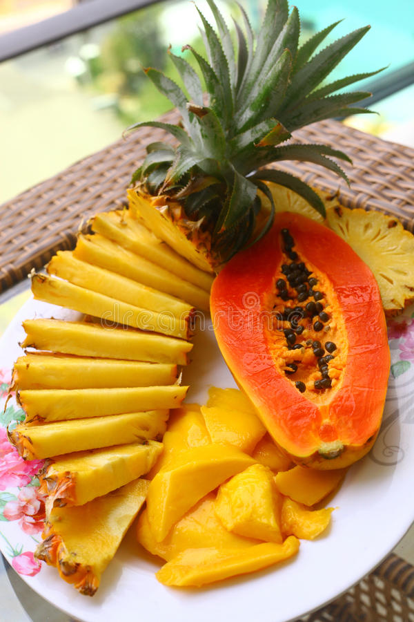 Tropical fruit pineapple, mango, corambola, papaya. On the plate served on palm tree for dietary light breakfast royalty free stock photos