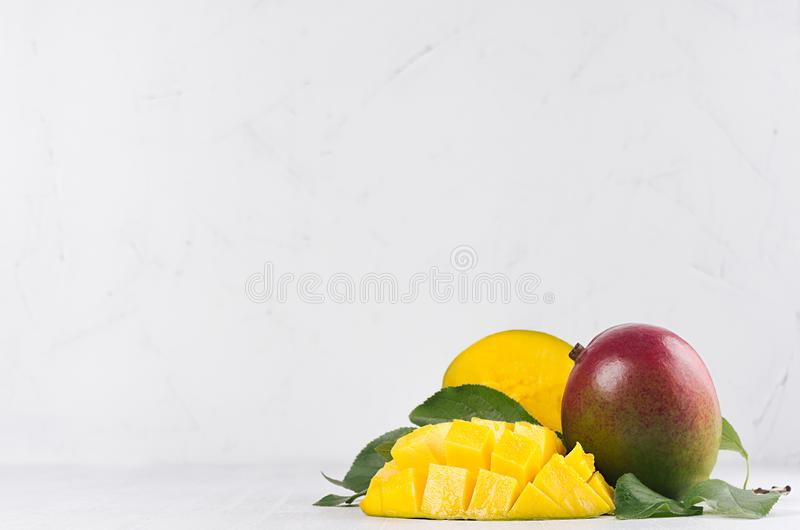 Tropical fruit red mango with juicy pulpy chopped slice and green leaves on white wooden background. Fresh summer fruit backdrop. Tropical fruit red mango with royalty free stock photos