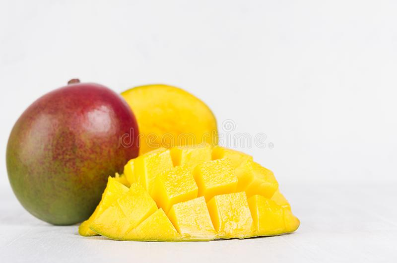 Tropical fruit red mango with juicy pulpy chopped slice on white wooden background. royalty free stock images