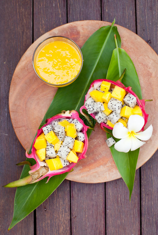 Tropical fruit salad in pitahaya, dragon bowls with mango juice. Tropical fruit salad in pitahaya, dragon fruit bowls with a glass of mango juice and flower on royalty free stock photos