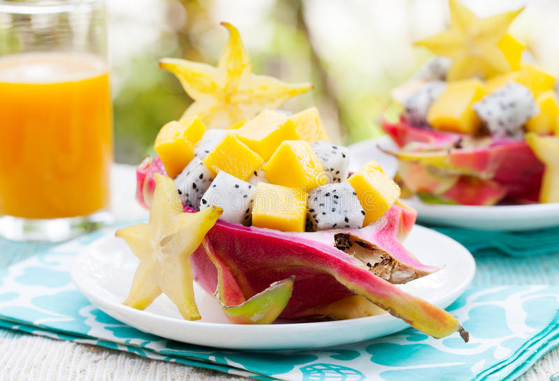 Tropical fruit salad in pitahaya, mango, dragon fruit bowls with a glass of juice. Diet, healthy fruit salad Healthy breakfast, weight loss concept stock photo