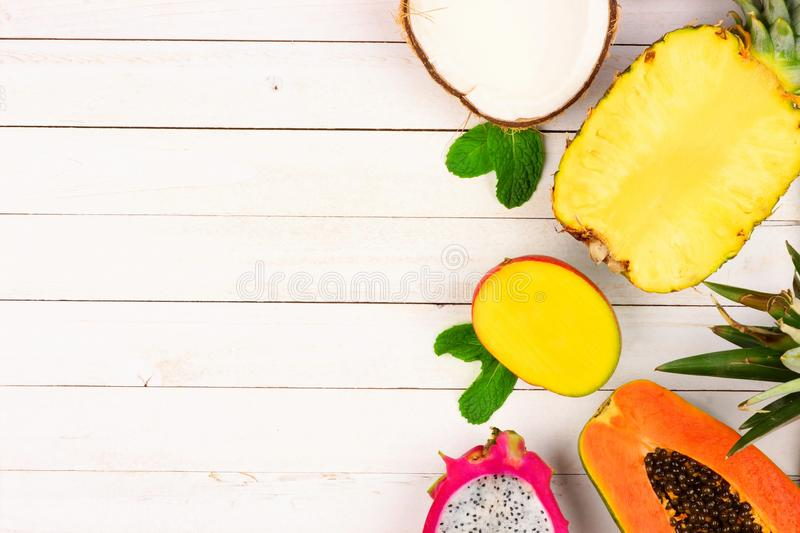 Tropical fruit side border on a white wood background stock photography