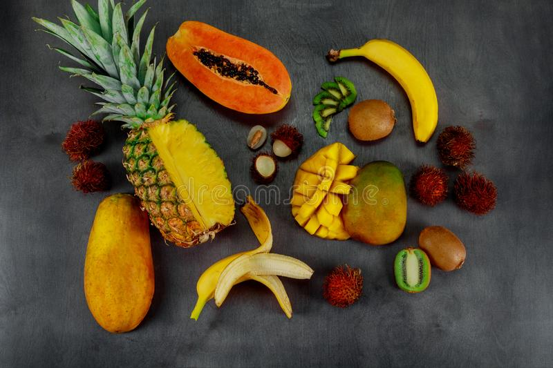 Tropical fruits assortment on a dark wood background with top view stock photo