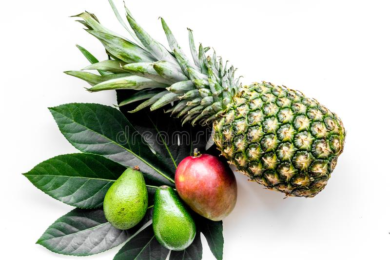 Tropical fruits background. Mango near exotic leaf and pineapple on white top view. Tropical fruits background. Mango near exotic leaf on white top view stock photography