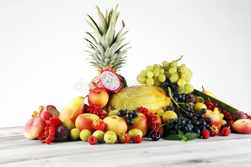 Tropical fruits background, many colorful ripe fruits with strawberries, grapes and cherries on wooden background. Tropical fruits background, many colorful ripe stock image