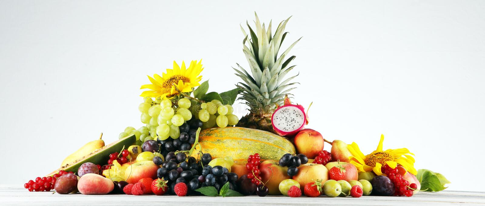 Tropical fruits background, many colorful ripe fruits with strawberries, grapes and cherries on wooden background. Tropical fruits background, many colorful ripe royalty free stock photo