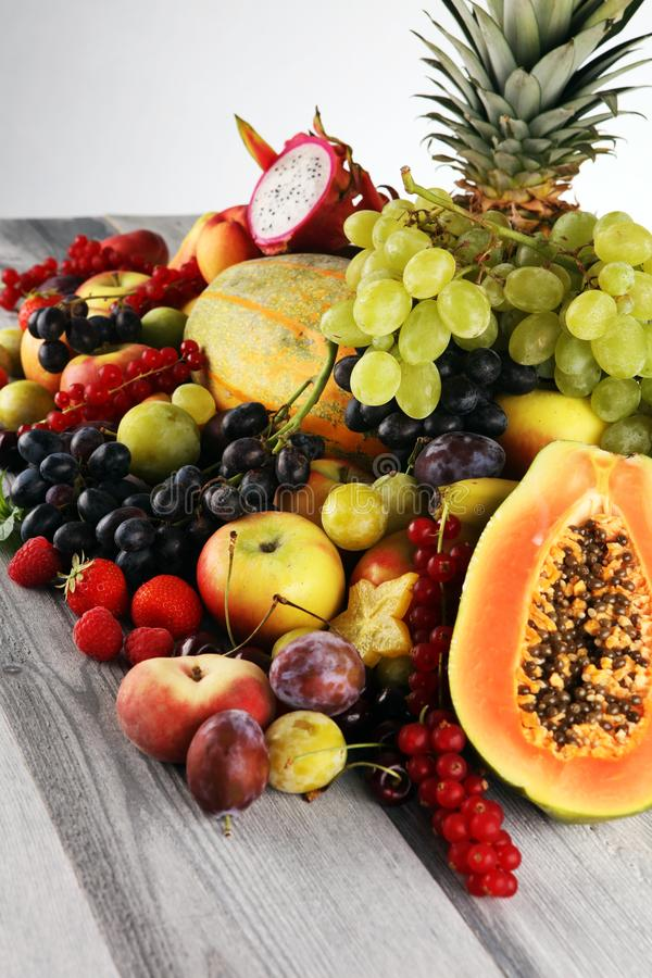 Tropical fruits background, many colorful ripe fruits with strawberries, grapes and cherries on wooden background. Tropical fruits background, many colorful ripe royalty free stock photos