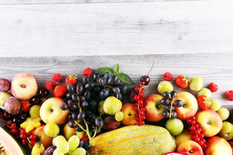 Tropical fruits background, many colorful ripe fruits with strawberries, grapes and cherries on wooden background. Tropical fruits background, many colorful ripe stock photography