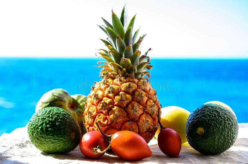 Tropical fruits collection, custard apple or green ripe cherymoia, passion fruit, pineapple, mango, tamarillo, avocado exotic. Fruits on blue sea background in stock image