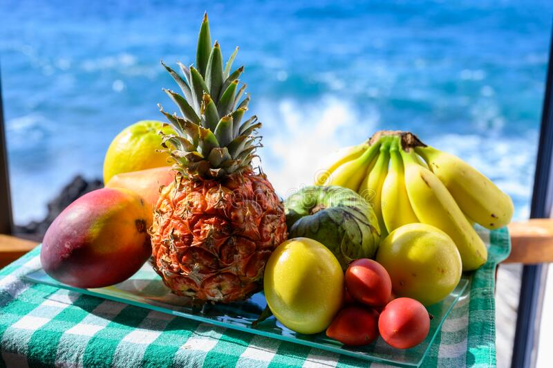 Tropical fruits collection, custard apple or green ripe cherymoia, passion fruit, pineapple, mango, tamarillo, banana exotic. Fruits on blue sea background in royalty free stock image