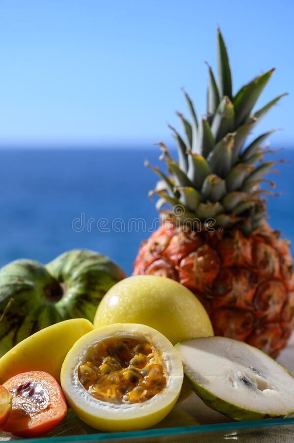 Tropical fruits collection, custard apple or green ripe cherymoia, passion fruit, pineapple, mango, tamarillo exotic fruits on. Blue sea background in sunny day royalty free stock photography