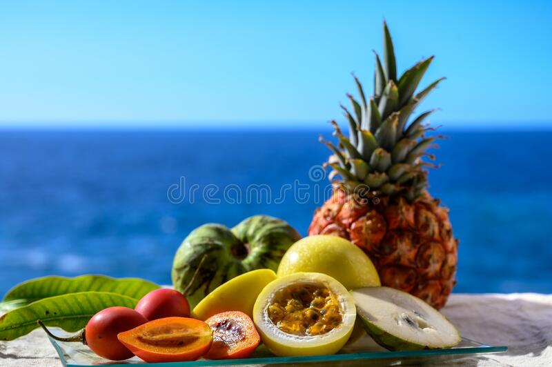 Tropical fruits collection, custard apple or green ripe cherymoia, passion fruit, pineapple, mango, tamarillo exotic fruits on. Blue sea background in sunny day royalty free stock photos