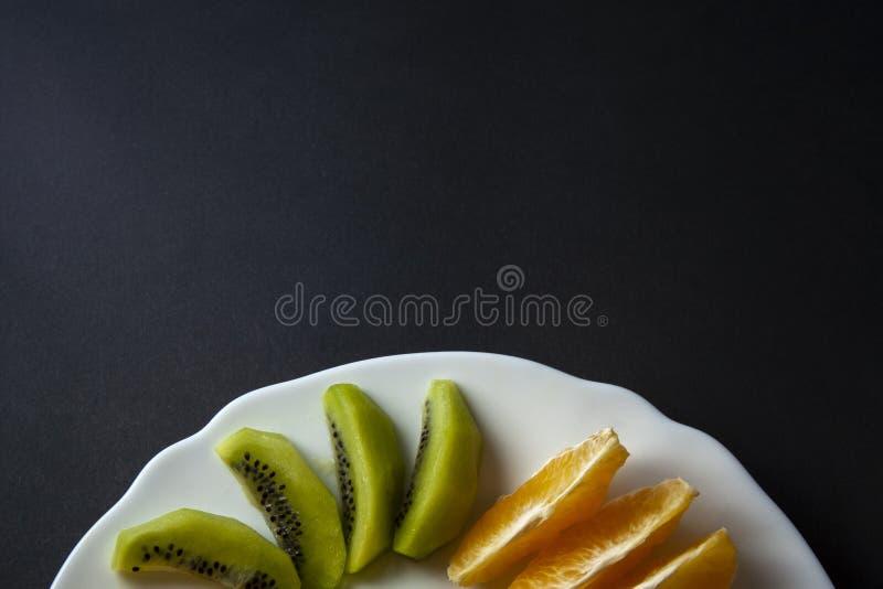 Tropical fruits, kiwi and mandarin orange slices placed on white stock photography