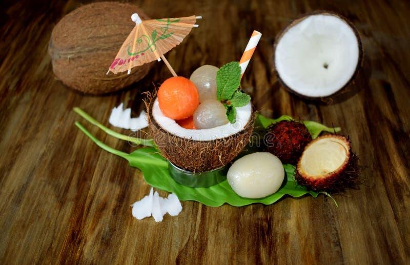 Tropical fruits: longan, rambutan and papaya ball-shaped pieces are lying in coconut royalty free stock photo