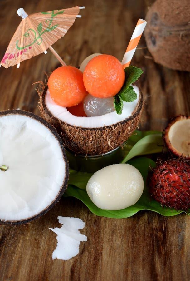 Tropical fruits: longan, rambutan and papaya ball-shaped pieces are lying in coconut royalty free stock images