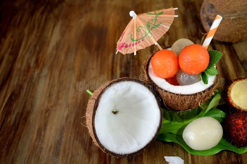 Tropical fruits: longan, rambutan and papaya ball-shaped pieces are lying in coconut stock images