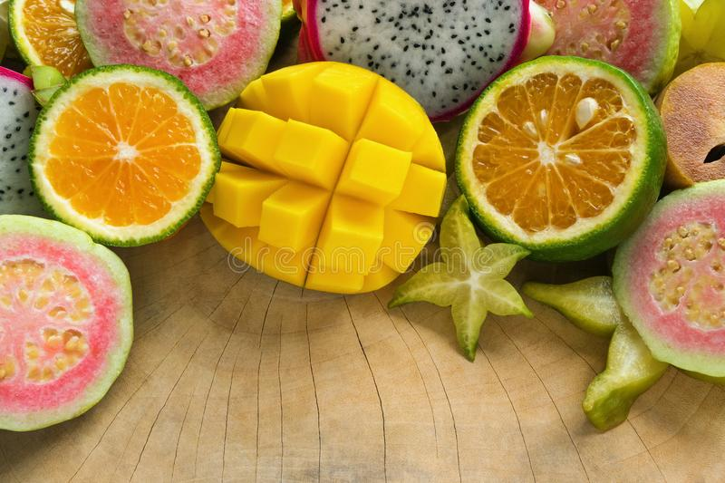 Tropical fruits mango, tangerine, guava, dragon fruit, star fruit, sapodilla on the wooden background. Bright colorful tropical fruits mango, tangerine, guava stock photo