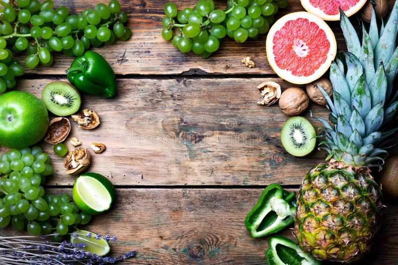 Tropical fruits and vegetables background. Pineapple, sweet pepper, grapefruit, kiwi, grapes, lime on a wodden background. Summer stock photography