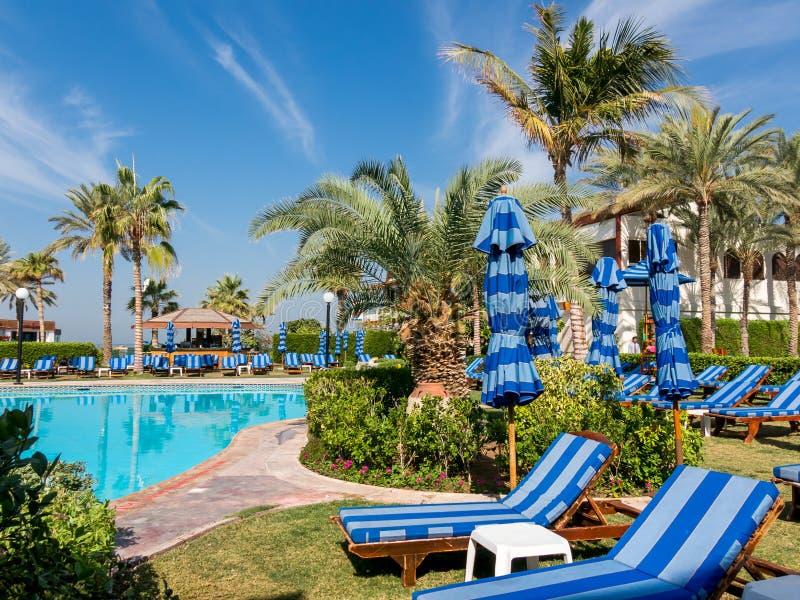 Tropical garden of luxury hotel in Dubai. Sunbeds, palm trees and pool in tropical garden of luxury hotel beach resort in Dubai, United Arab Emirates stock images