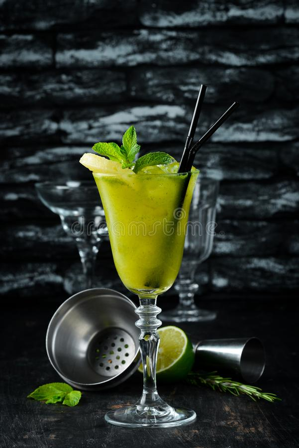 Tropical Green Alcoholic Cocktail. Rum, mint, and pineapple juice. Alcoholic cocktail in a glass. On a wooden background. stock photos