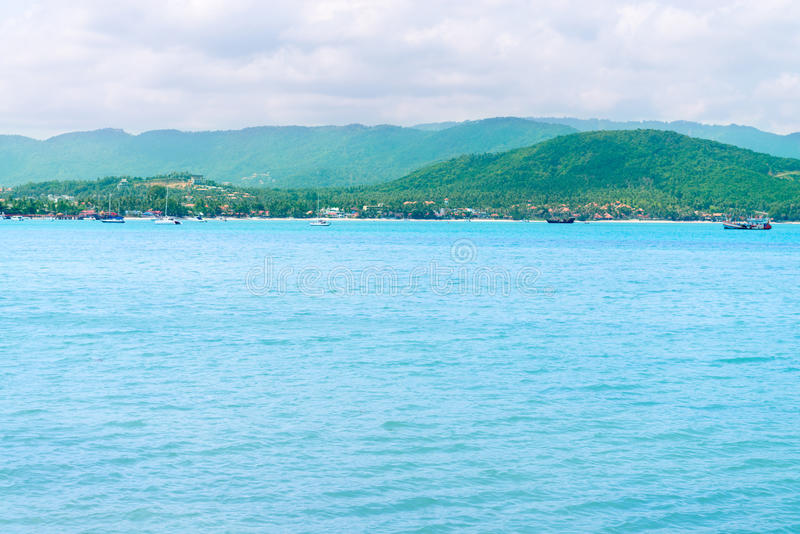Tropical green hilly island shore and blue calm clean sea. On the front stock photo