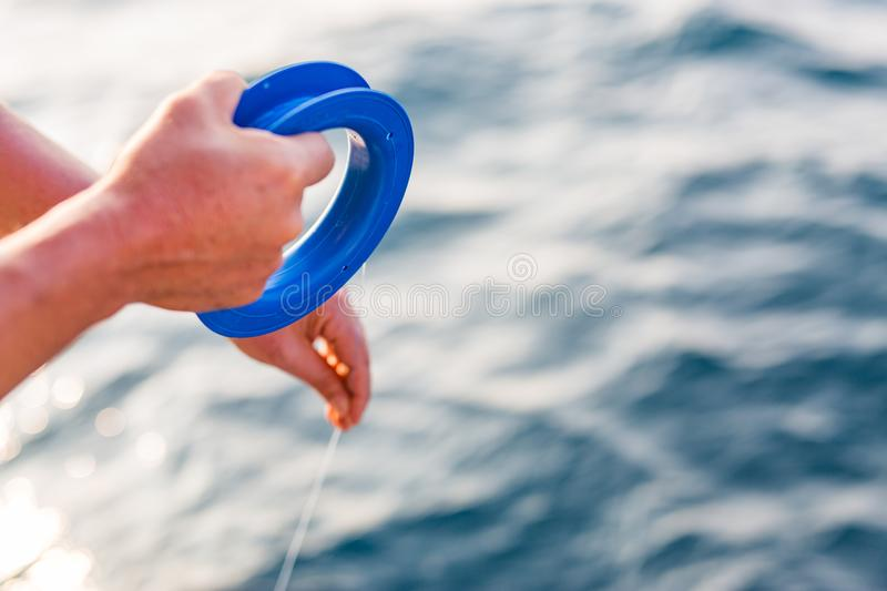 Tropical hand fishing in sunset time. Fishing line and hand, blurred sea background royalty free stock photography