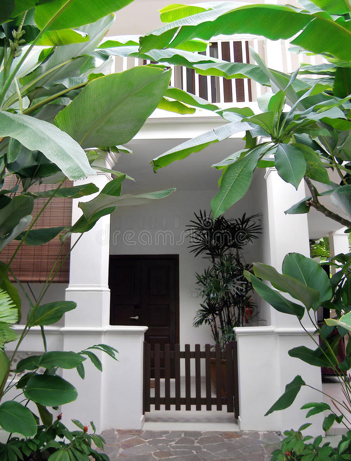 Tropical house with lush garden. A photograph showing the entrance door of a beautiful tropical style two storey villa house in southeast asia, painted in white royalty free stock images