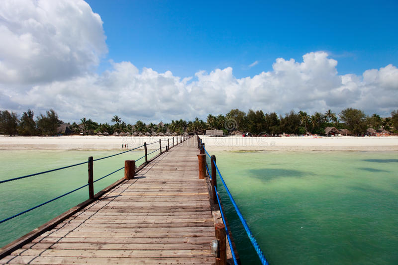 Tropical island. Wooden jetty leading to exotic beach of tropical Zanzibar island royalty free stock images