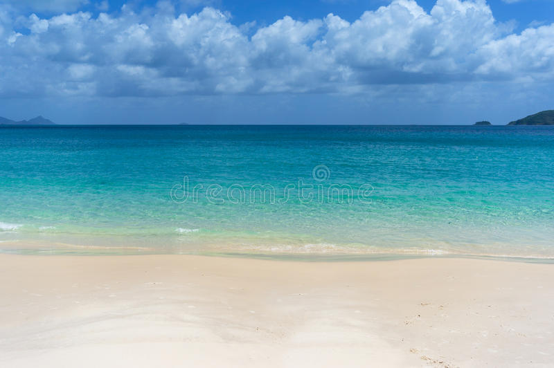Tropical island beach with white sand and crystal clear water. Tropical island beach with white sand and crystal clear turquoise water. Summer vacation stock image