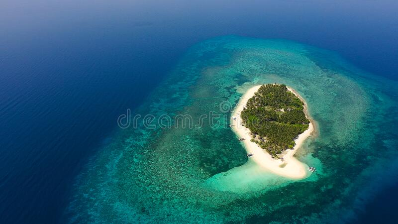 Tropical island on a coral reef, top view. Digyo Island, Philippines. Tropical island on a coral reef, top view. Beautiful white sandy beach for tourists.Digyo stock photos