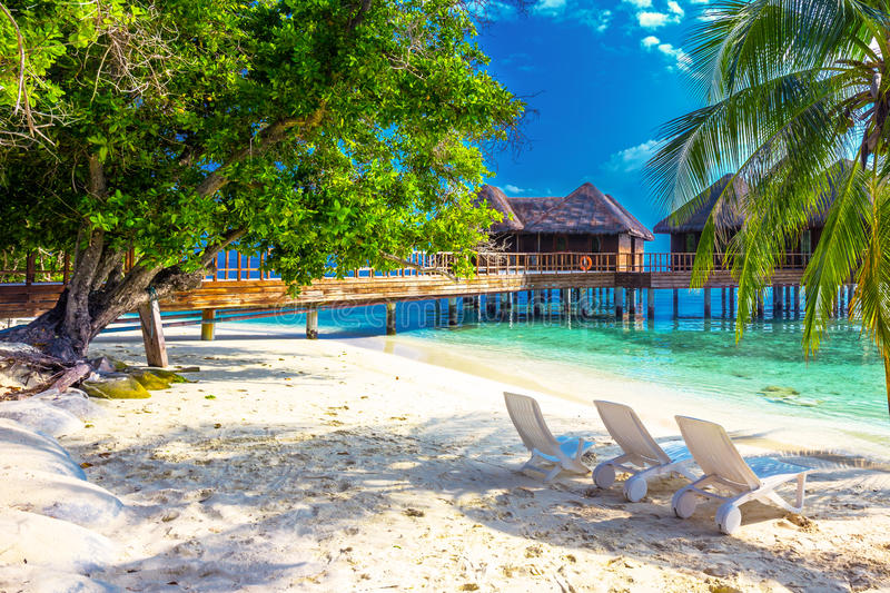 Tropical island with sandy beach, palm trees, overwater bungalows and tourquise clear water. royalty free stock photo
