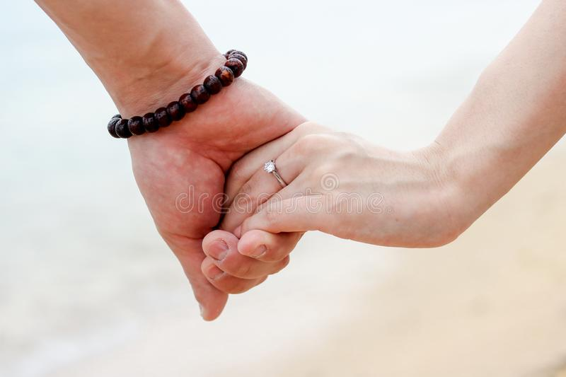 Beautiful young couple hand in hand stock image
