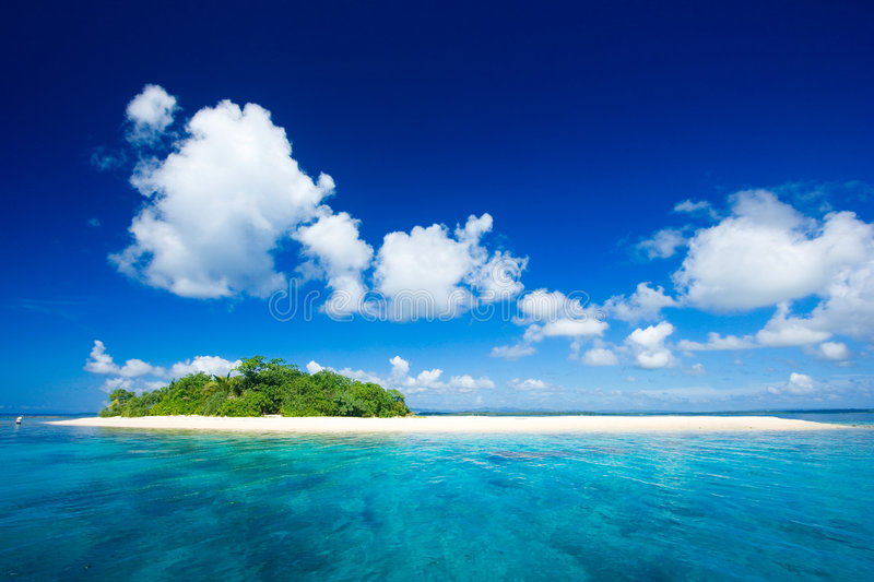 Tropical island vacation paradise. Beautiful tropical island vacation paradise with white sand, tall palm trees, fluffy white clouds, a dark blue sky and stock photos