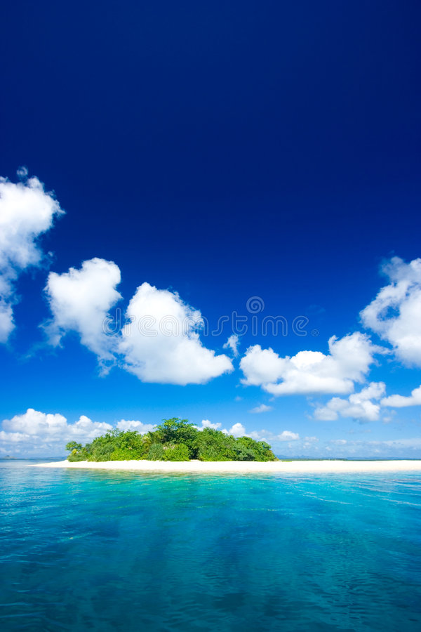 Tropical island vacation paradise. Beautiful tropical island vacation paradise with white sand, tall palm trees, fluffy white clouds, a dark blue sky and royalty free stock photo