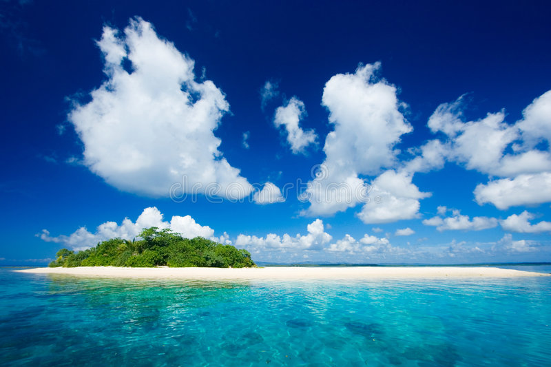 Tropical island vacation paradise. Beautiful tropical island vacation paradise with white sand, tall palm trees, fluffy white clouds, a dark blue sky and royalty free stock image