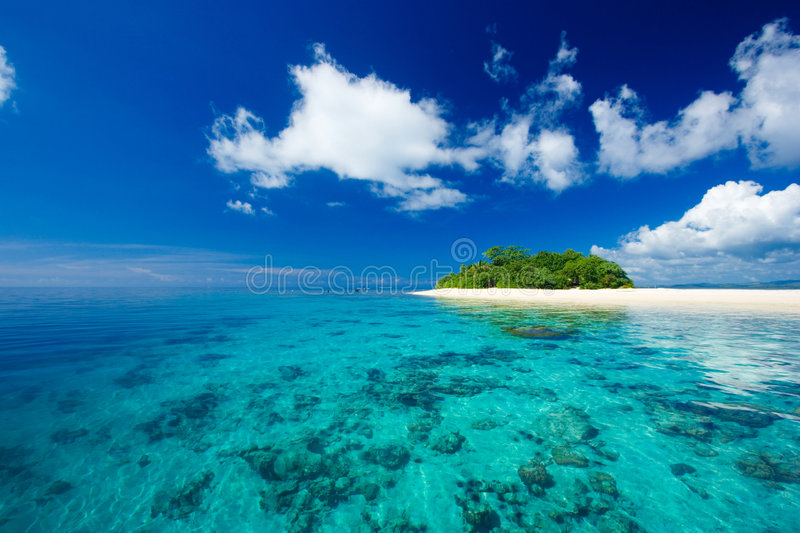 Tropical island vacation paradise. Beautiful tropical island vacation paradise with white sand, tall palm trees, fluffy white clouds, a dark blue sky and stock image
