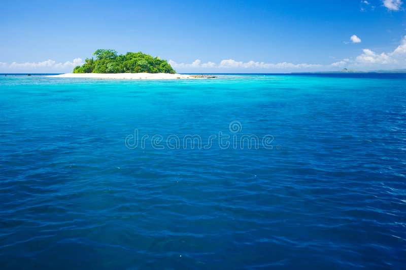 Tropical island vacation paradise. Beautiful tropical island vacation paradise with white sand, tall palm trees, fluffy white clouds, a dark blue sky and stock photo