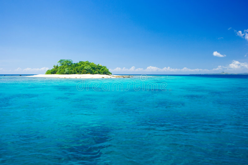 Tropical island vacation paradise. Beautiful tropical island vacation paradise with white sand, tall palm trees, fluffy white clouds, a dark blue sky and stock images