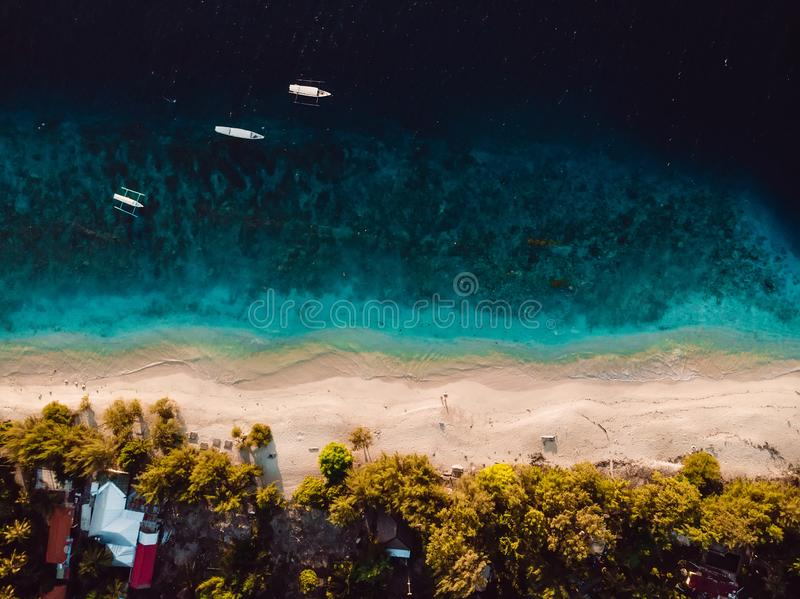 Tropical island with village, beach and turquoise crystal ocean, aerial view. Gili islands. Tropical island with beach, boats and turquoise crystal ocean, aerial royalty free stock photo