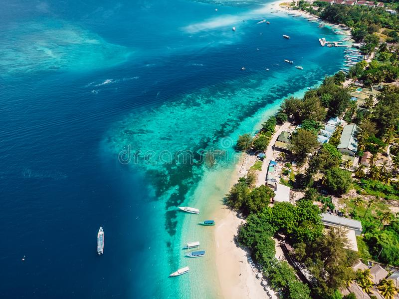 Tropical island with village, beach and turquoise crystal ocean, aerial view. Gili islands. Tropical island with beach, boats and turquoise crystal ocean, aerial royalty free stock image