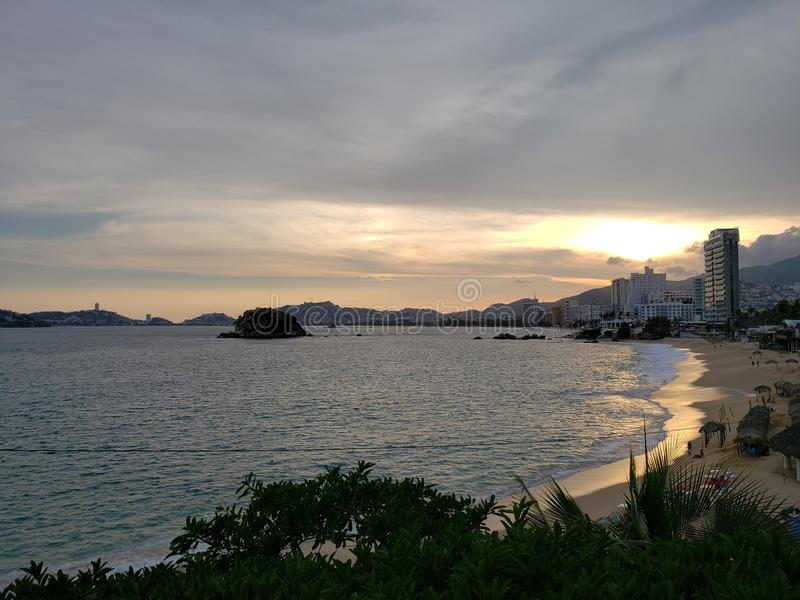 Tropical landscape in the main bay of Acapulco, Mexico during sunset. Travel, tourism, vacation, water, sea, ocean, mexican, beach, coast, sky, evening, dusk stock photography