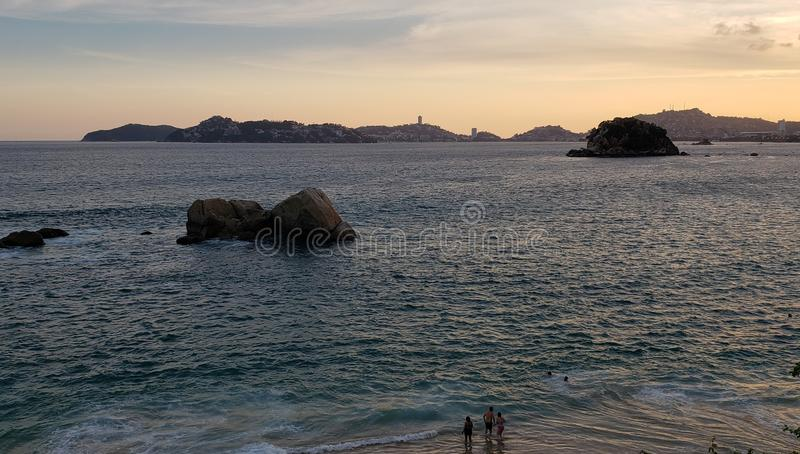 Tropical landscape in the main bay of Acapulco, Mexico during sunset. Travel, tourism, vacation, water, sea, ocean, mexican, beach, coast, sky, evening, dusk stock photo