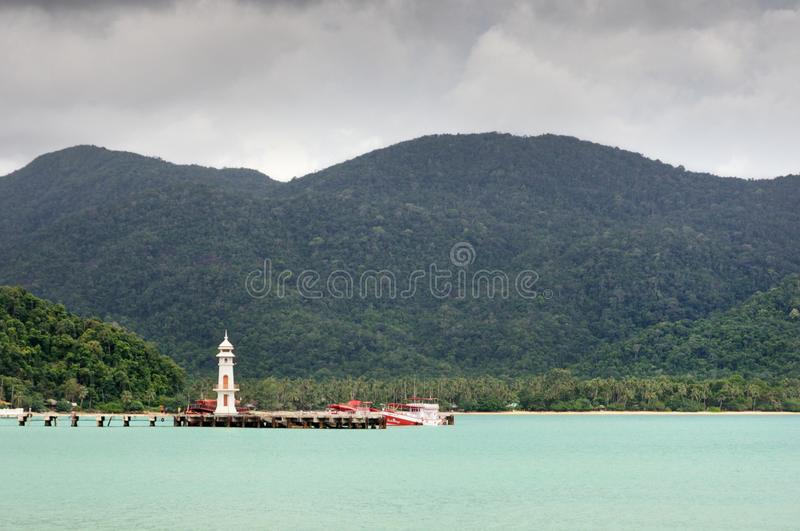 Tropical landscape with turquoise tropical sea, white lighthouse, fishing boat, Bang Bao pier and Koh Chang island on horizon royalty free stock photography