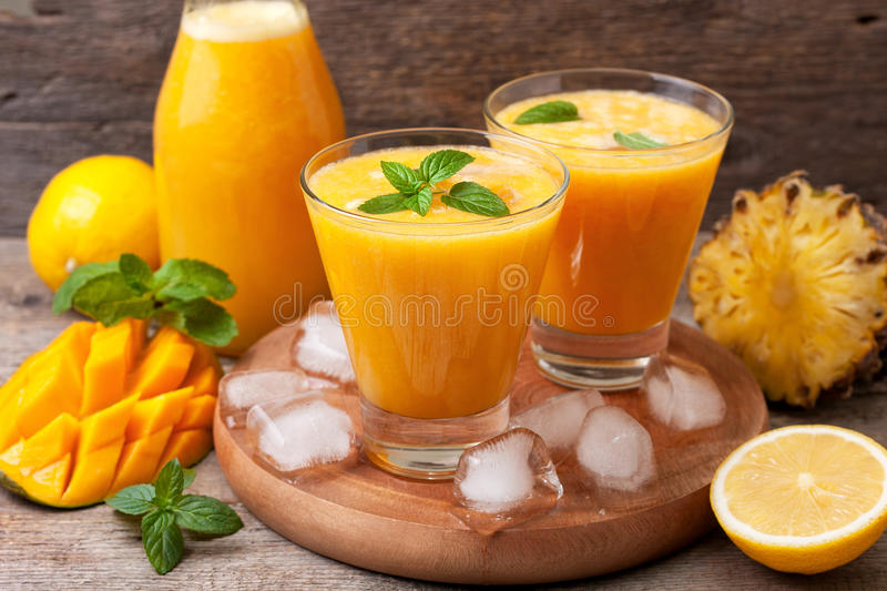 Tropical lemonade with mango and mint. Tropical lemonade with mango, pineapple and mint in glasses and bottle on old wooden background stock photos