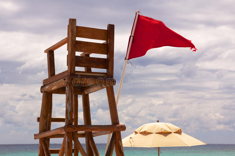 Tropical Lifeguard Post. Lifeguard post at a tropical beach stands abandoned as red flag waves in the wind stock images