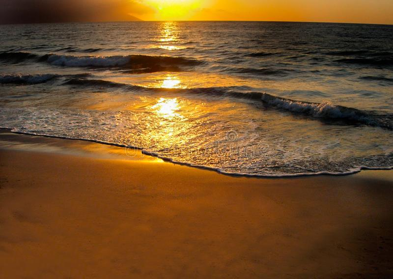 Ocean Sunset on Beach Copy Space. Tropical location of golden sunset with soft waves of incoming tide. Copy space in horizontal layout stock photo
