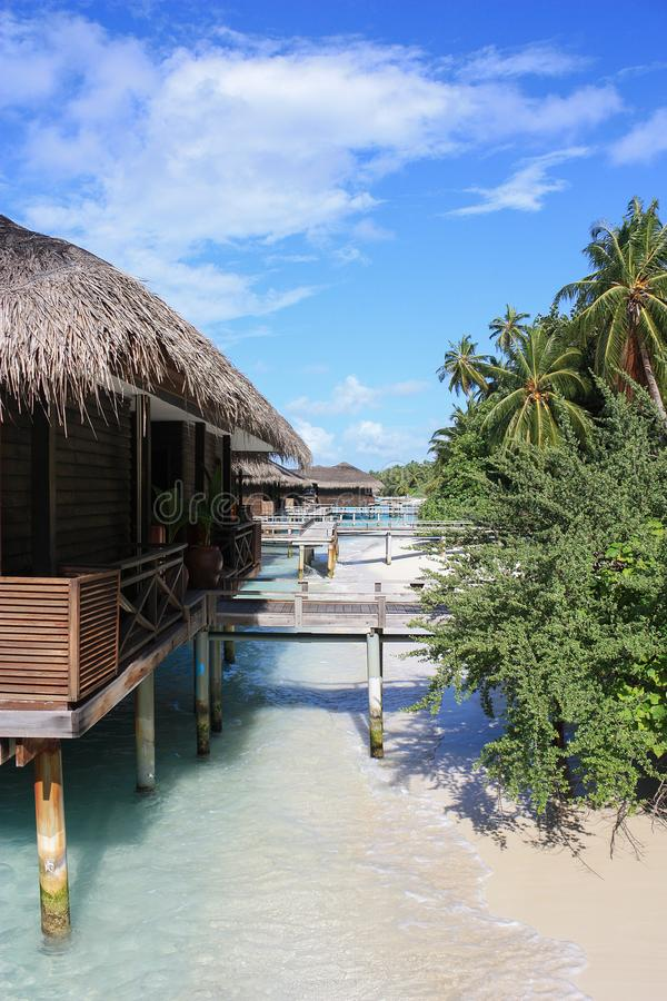 Tropical Maldives island resort on a sunny day. Luxury water villas and bungalows with thatch roofwhere you can fealing royalty free stock images