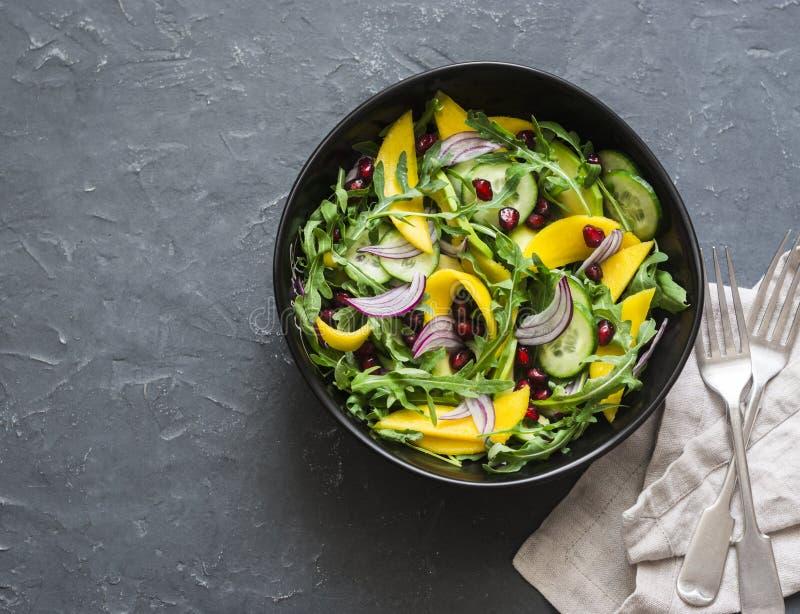 Tropical mango, avocado, cucumber, arugula salad. Delicious healthy vegetarian food. On a dark background. Top view royalty free stock photos