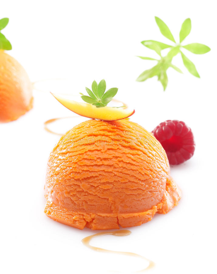 Tropical mango icecream dessert. Single scoop of a colourful orange tropical mango icecream dessert on a white background royalty free stock image