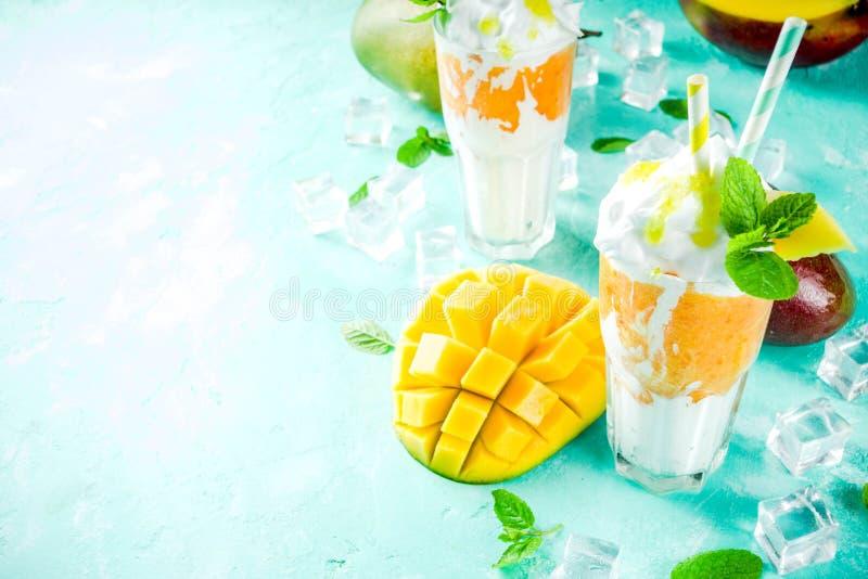 Tropical mango milkshake. Tropical sweet dessert drink. mango milkshake or smoothie cocktail, with mango slices, mint and ice cubes, light blue background copy royalty free stock images